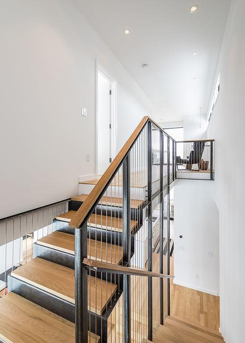 Minarik Architecture staircase metal suspension wood railings wood steps stairwell white walls modern house