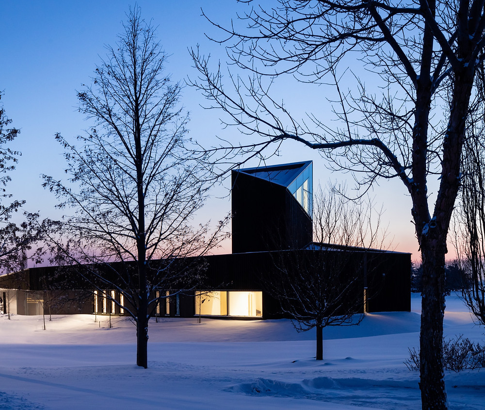 Black building with tower in snowy winter landscape at dusk with lights on
