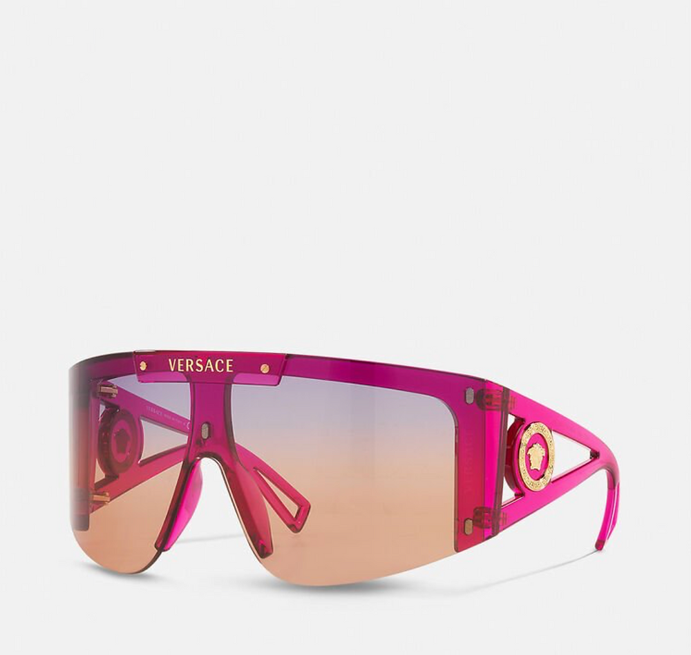Shield sunglasses are within range. The wrapped semi-rim shield style features wide and hollow tapered temples in a bold pink frames and gradient orange to purple lenses.