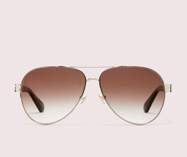 Geneva is Kate Spade's sleek update to the classic. Shiny metal with scratch-resistant gradient lenses, gold frame, brown bronze lens, pink background