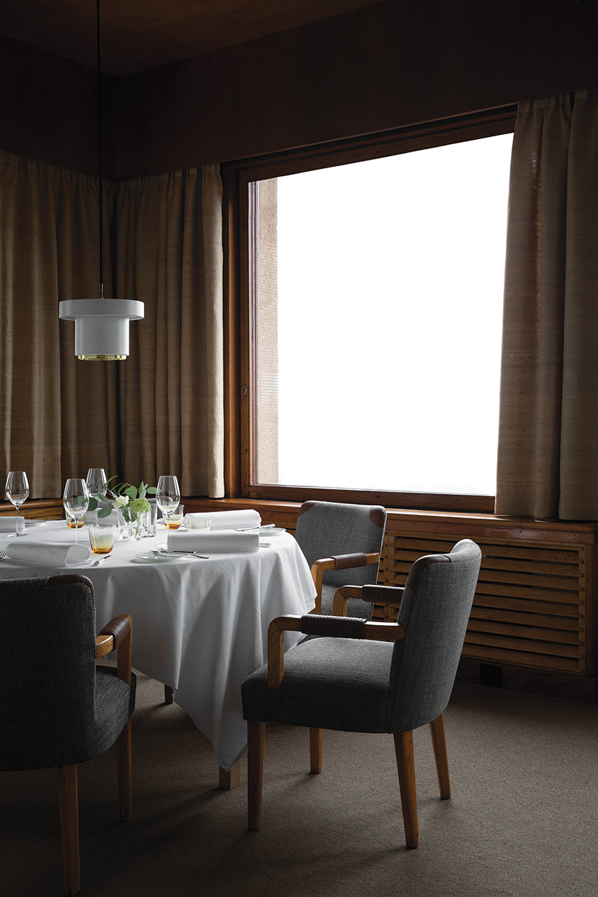 Savoy restaurant Helsinki dining room with picture window, draperies, Artek pendant light, place settings, white tablecloth, round table, gray upholstered side chairs