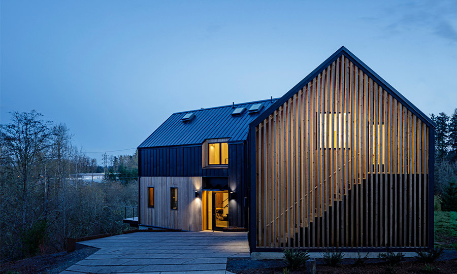 Minarik Architecture house exterior, dusk, blue sky, wood slats, outdoor staircase, windows, lights on, patio