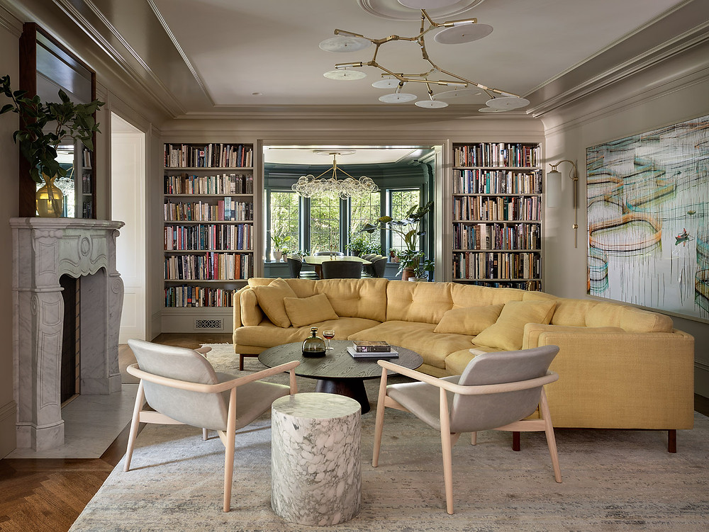 Albemarle Terrace House  Jessica Helgerson Interior Design living room tan walls yellow sofa armchairs marble fireplace large painting ceiling light fixture crown molding modern sconce library book cases view into dining room green walls