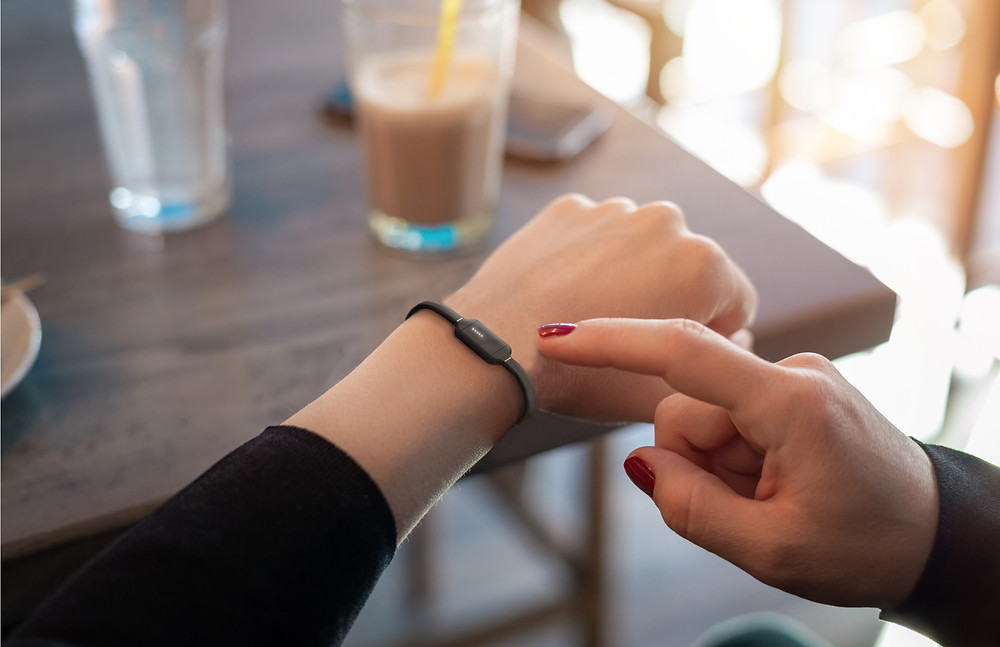 Lo high blood pressure monitor bracelet on woman's wrist at cafe with black sleeve and red nail polish with cell phone on table and iced latte