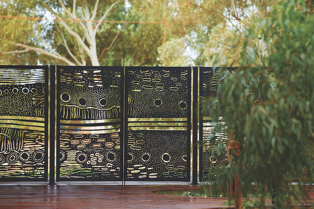 Artistic metal gate surrounded by trees. The Puntukurnu Aboriginal Medical Service clinic in Newman, Western Australia, sits about 870 miles from Perth and is the first primary health care facility to be constructed in Newman. A screen in the entryway incorporates a design from a community-based artist. Both photographed by Robert Frith, Acorn Photo.