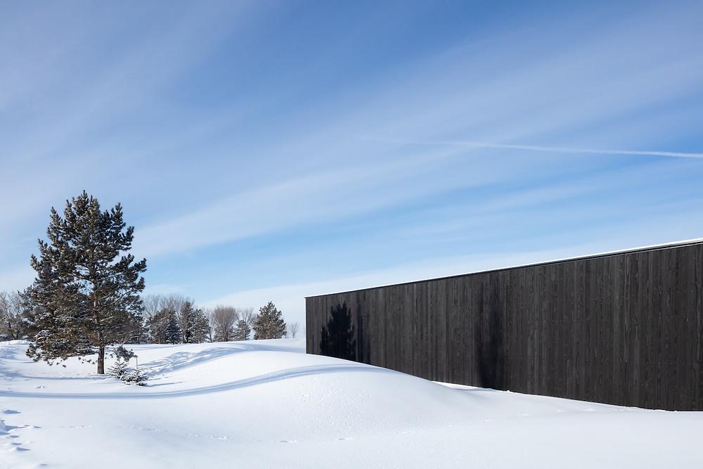 side of black wood building in snow landscape