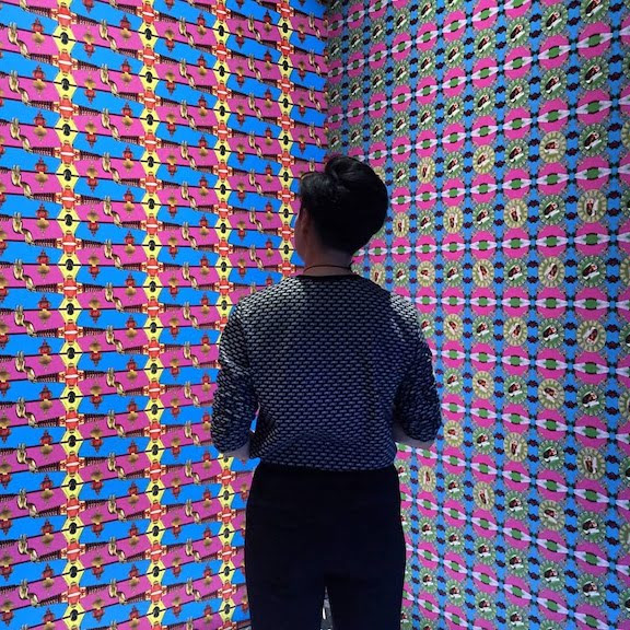 woman at exhibit of scratch and sniff wallpaper