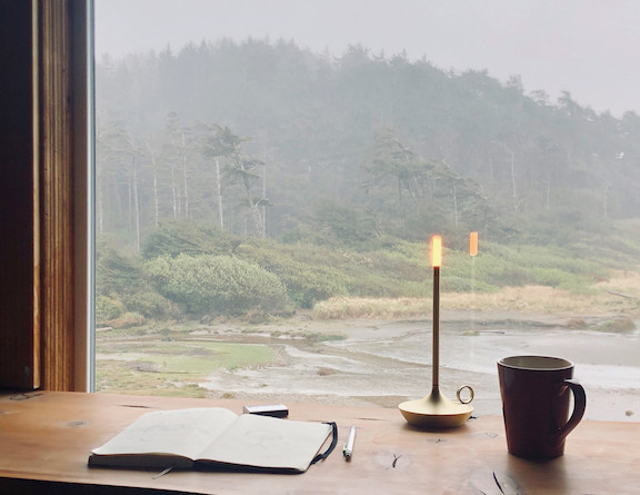Graypant's Wick candlestick light on a desk in the window overlooking coastal waterfront with evergreen trees, sea grass, show and waves