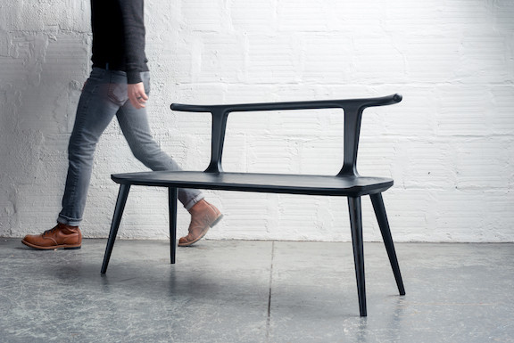 Black wood bench in industrial setting, man walking by