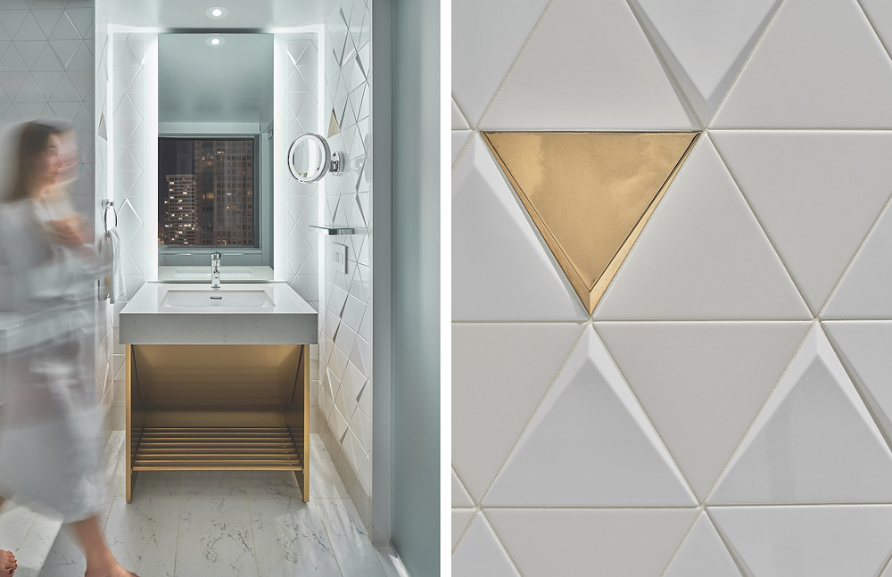 Hotel bathroom woman in robe white tile and marble gold vanity triangle tile gold triangle