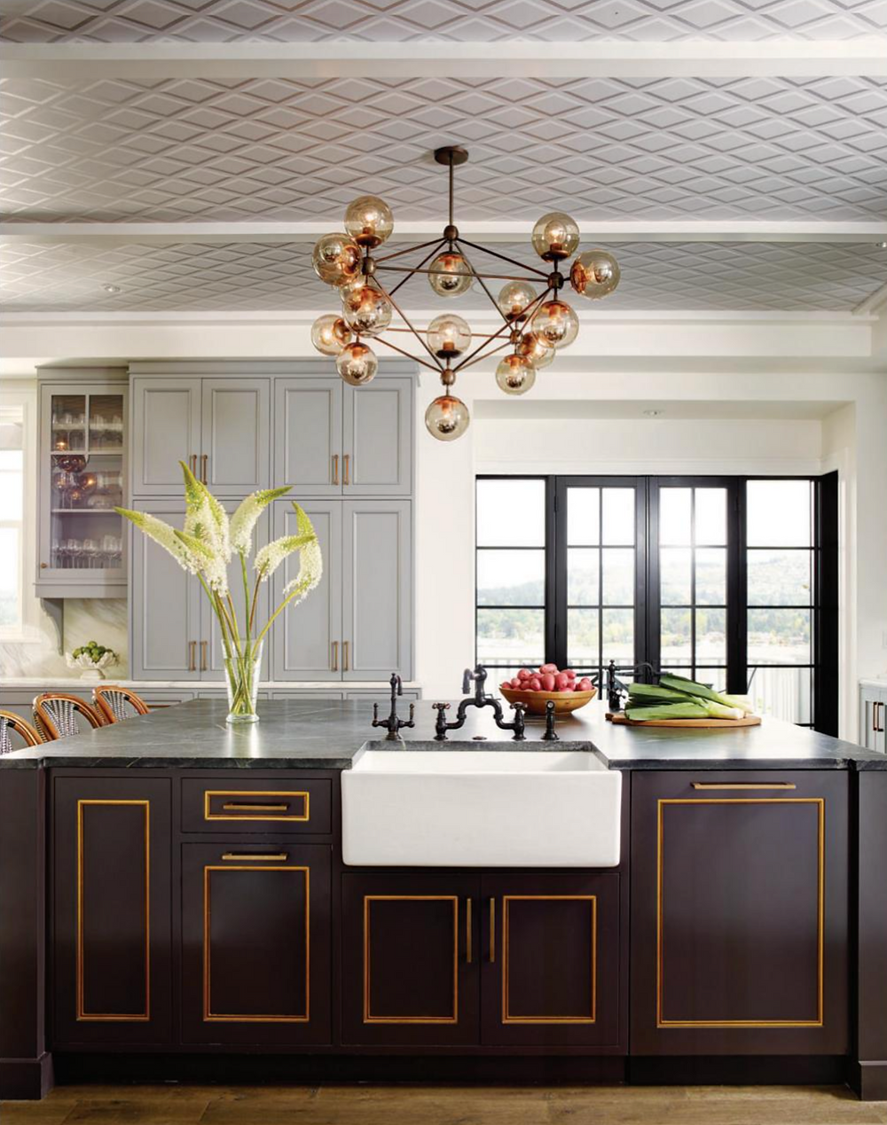 kitchen with wallpaper on ceiling, globe chandelier, black island with apron sink, gray cabinet, bronze