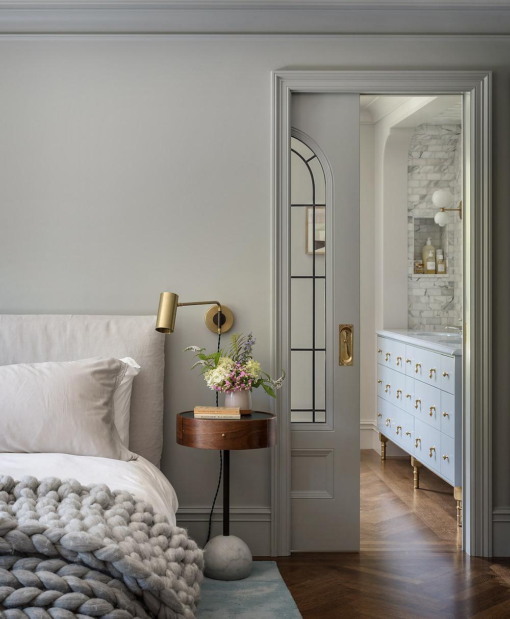 gray bedroom pocket door to bathroom storage vanity bed with chunky knit blanket globe light