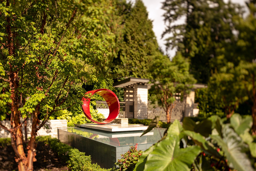 Modern garden sculpture, lush landscape, water feature, arbor