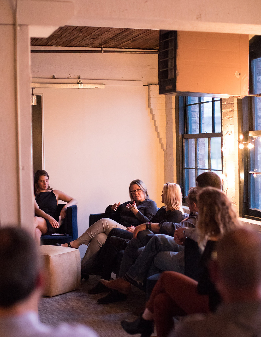 GRAY editor Rachel Gallaher moderates panel discussion with Kirsten Murray, FAIA, Chad Dale, Peter Steinbrueck, FAIA, Jenna Thornton, on blue sofa, loft style, Seattle office