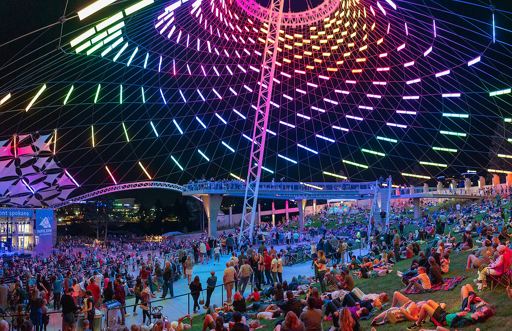 Pavilion at night with colored lights and crowd of visitors at Spokane's Riverfront Park