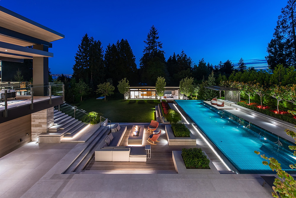 Night, modern landscape with infinity pool, patio, decks, outdoor seating, outdoor fireplace, red outdoor rocking chairs, modern art, pool house