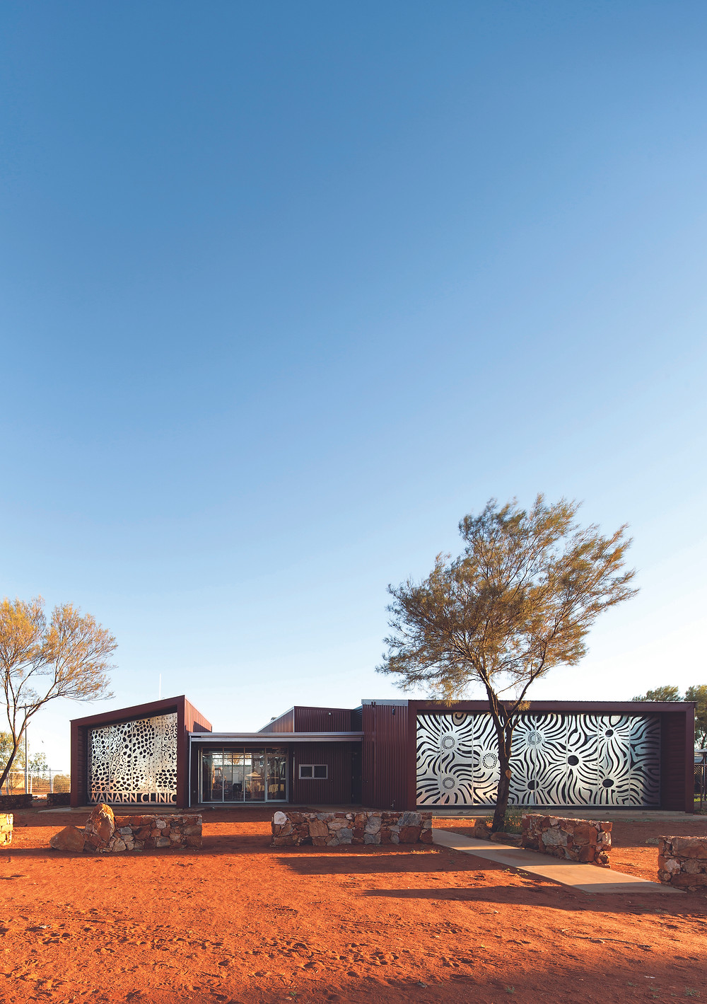 Building exterior in Western Australia desert with artistic wall panels. The Wanarn Clinic is a treatment venue operated by the Ngaanyatjarra Health Service in Western Australia. Located in the desert, the facility needed to be able to resist high temperatures and dusty conditions but, because of limited resources, operate at a low cost.