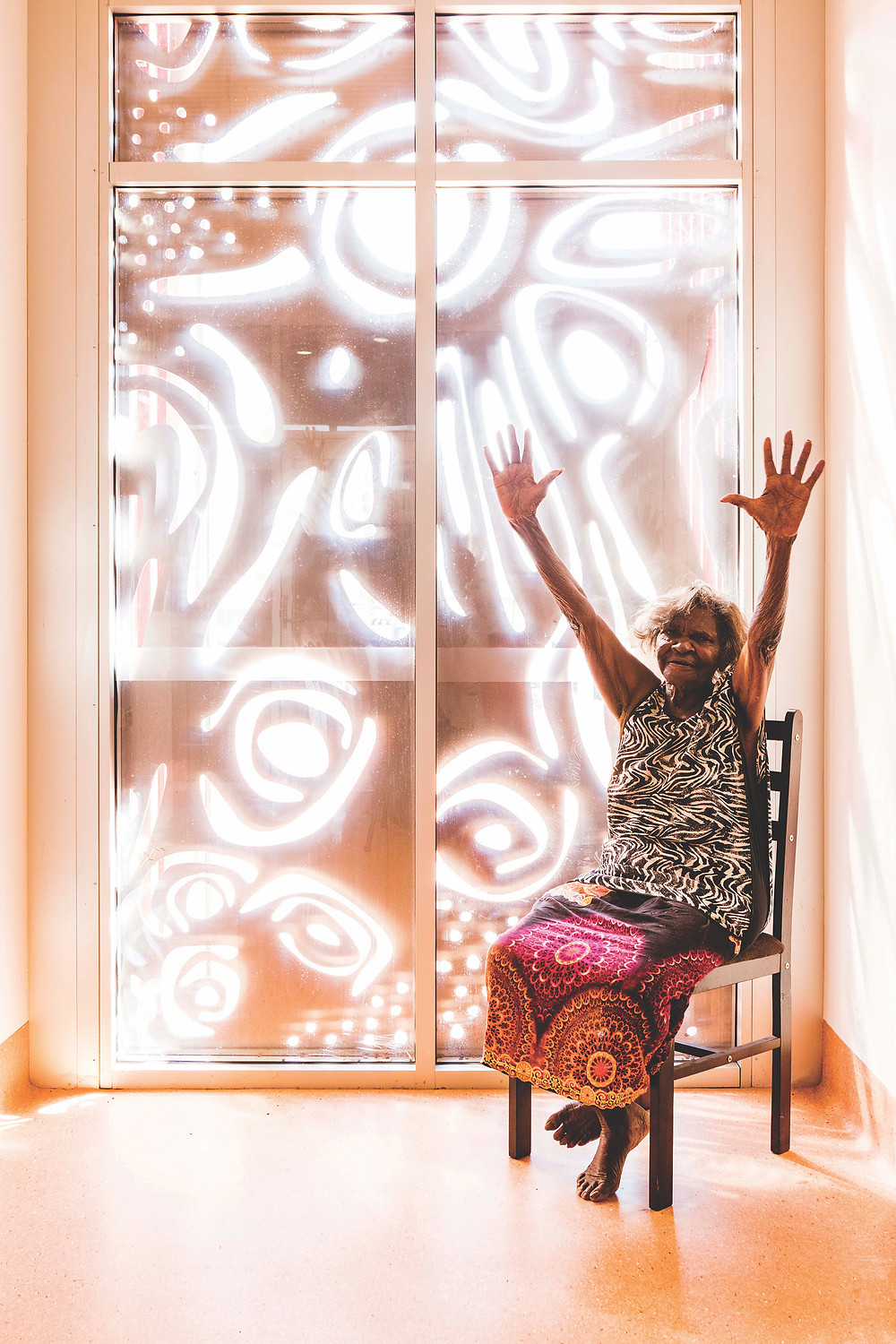 Aboriginal woman in chair with hands up in front of window art. Punmu artist Jakayu Biljabu sits in front of the screen she designed for the Punmu Aboriginal Health Clinic in the Western Australian desert. The clinic was designed by Kaunitz Yeung Architecture in deep collaboration with the local community, taking into consideration its unique cultures and customs.
