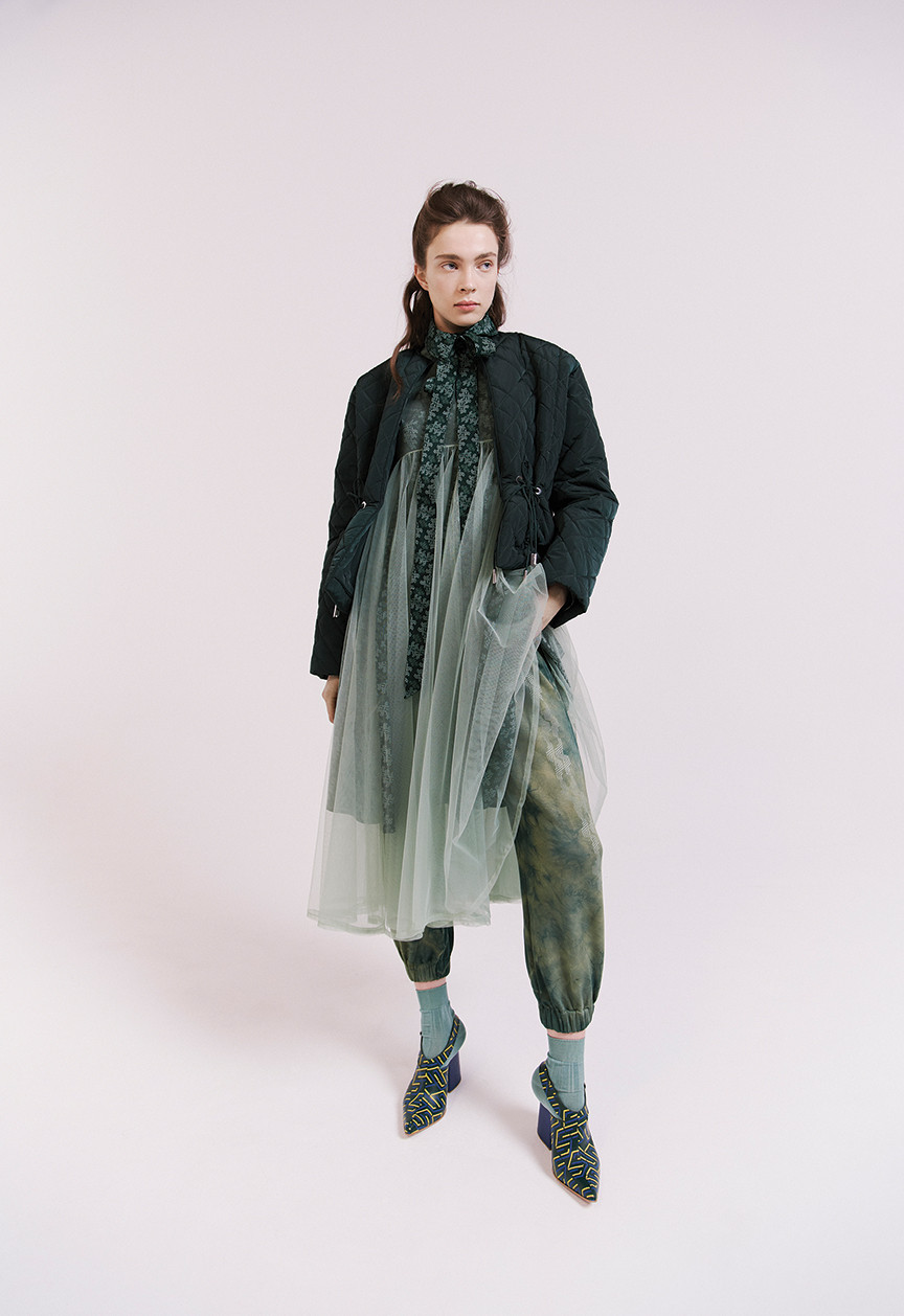 A look from Katie Ann McGuigan's AW20 collection features a nylon coat atop a tulle dress, patterned silk shirt, and '80s-inspired joggers. Geometric-printed shoes in a matching green hue complete the ensemble.