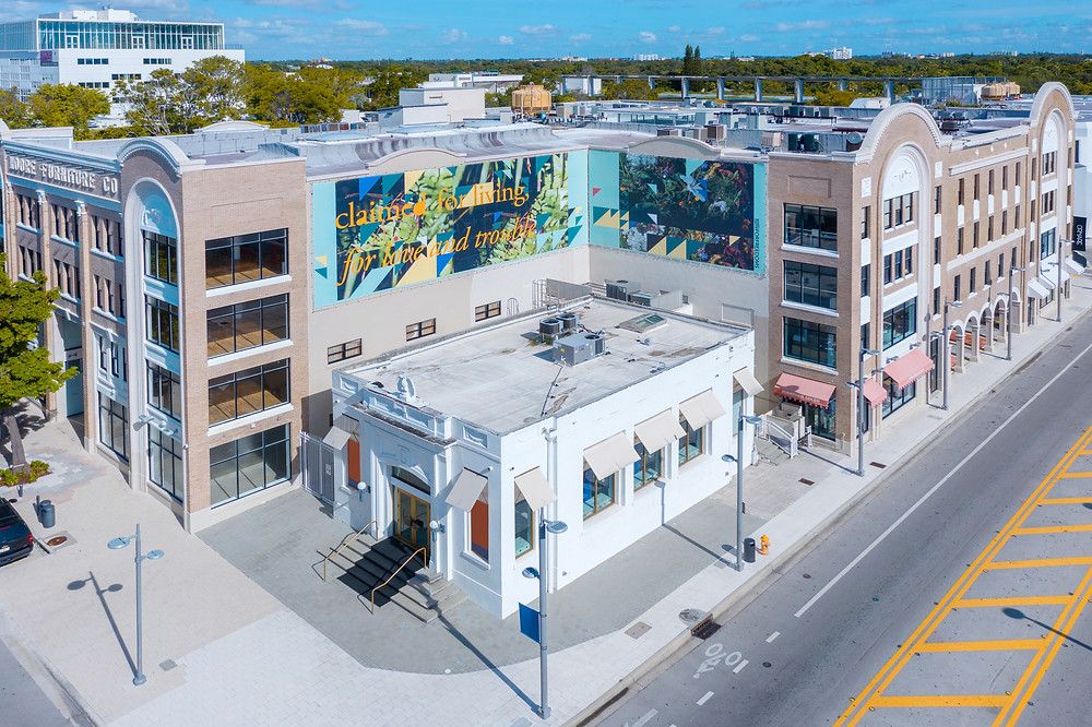 Aerial view of The Moore Building, in Miami Design District featuring billboard artwork by Adler Guerrier, in partnership with For Freedoms.