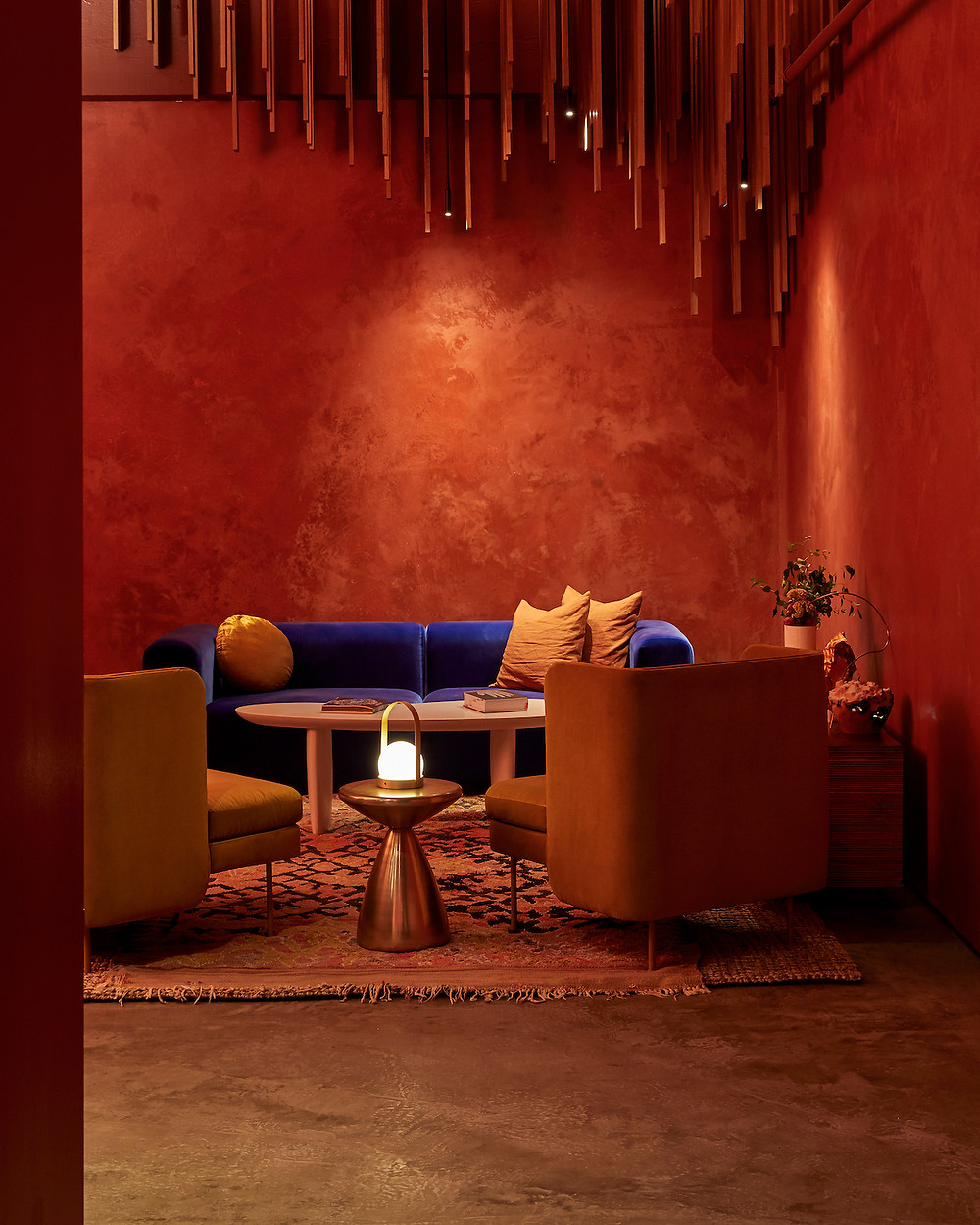Burnt orange walls with texture, ceiling feature, cobalt blue velvet sofa, velvet gold chairs