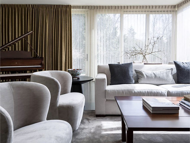 Hyde Evans Design luxurious living room with gold silk drapes and sheers, grand piano, gray velvet swivel chairs, comfy sofa with pillows, coffee table with art books