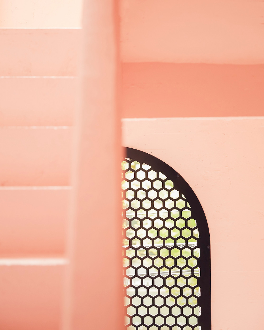 pink stairs, pink walls, arched window with grate