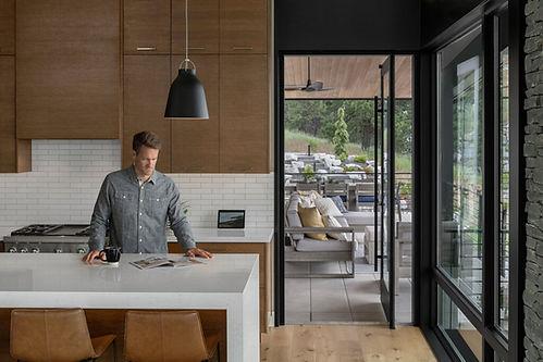 man in modern kitchen reading magazine drinking coffee northwest modern kitchen design outdoor space with rural landscaping modern patio furniture