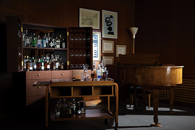 Savoy restaurant Helsinki custom bar cabinet design by StudioIlse with bottles of liquor, grand piano, dark brown walls, floor lamp, gallery style art