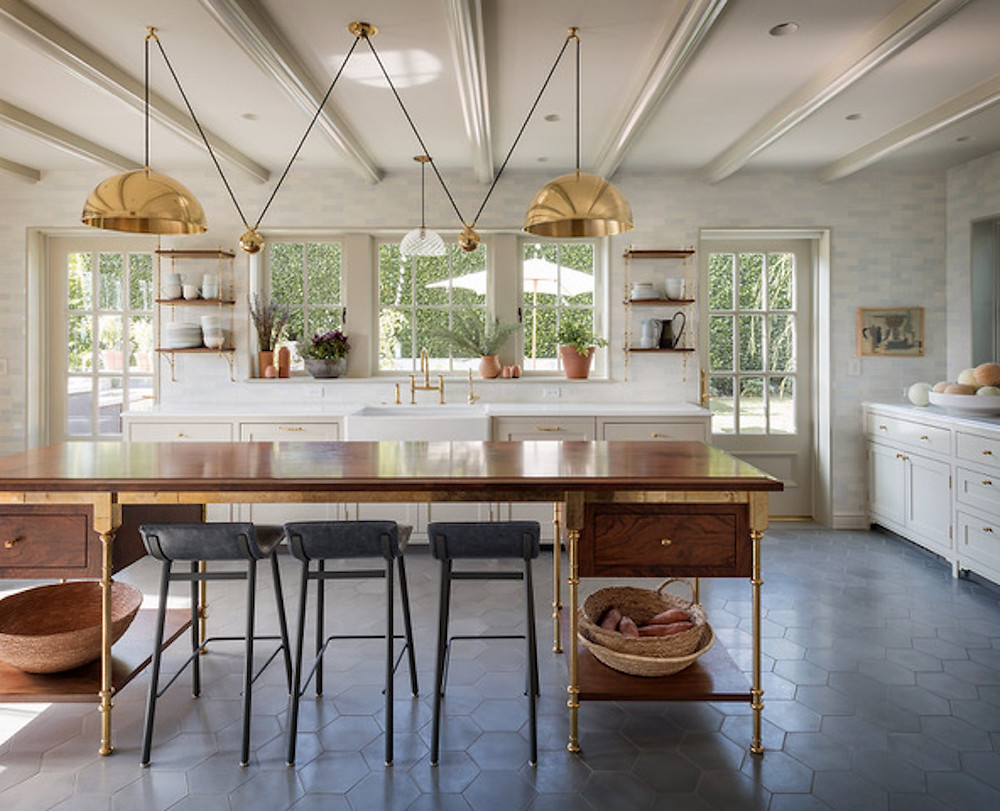 farmhouse kitchen with tile floor, gold pendants, gold accents, farm table island, black bar stools, apron sink, open shelving