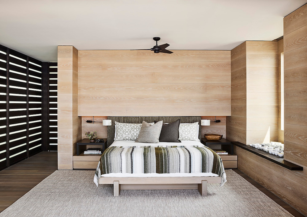 beach house bedroom wood clad walls slat walls window bench striped bedspread, built in nightstands ceiling fan