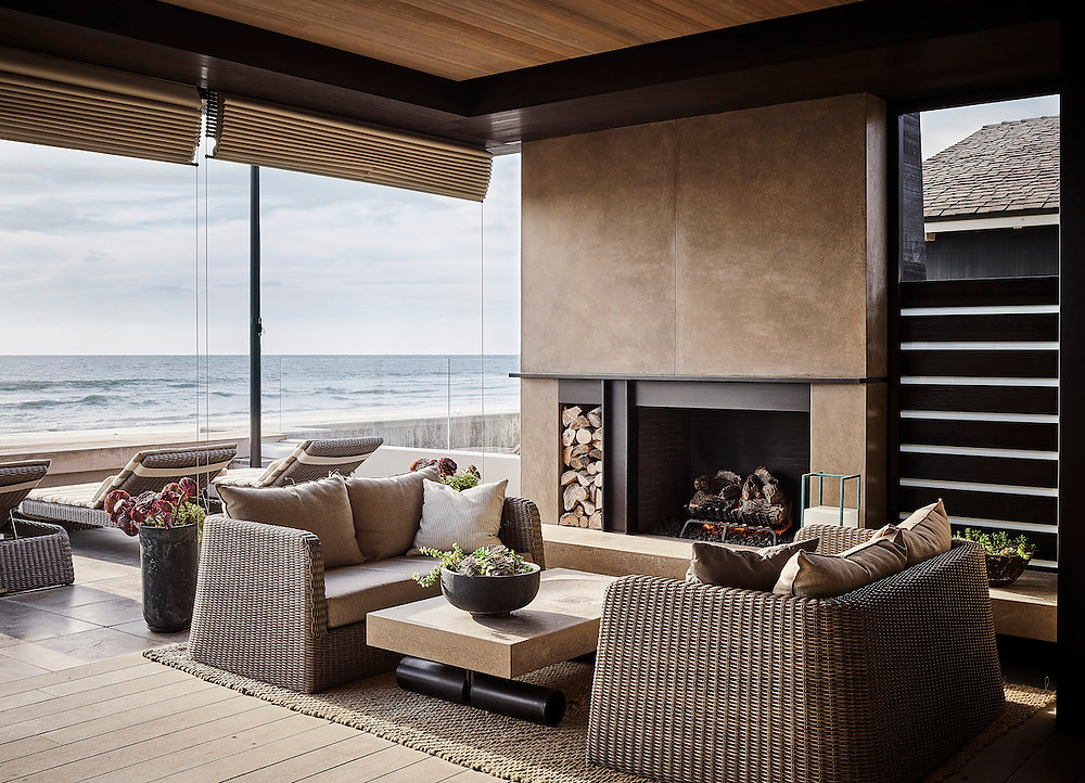 Auckland New Zealand modern beach house outdoor patio with fireplace, outdoor seating lounges