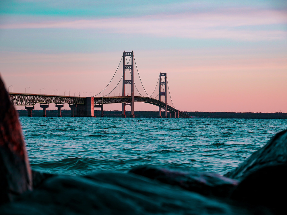Mackinac Bridge at sunset with a vibrant blue and pink sky.
