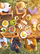 group sharing a meal outside on a wood table