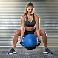 Sportif Femme de levage d'une Medicine Ball