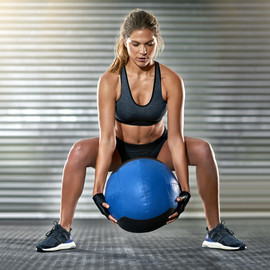 Sporty Woman Lifting a Medicine Ball