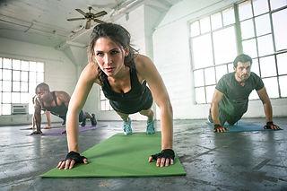 woman doing push ups on a green mat
