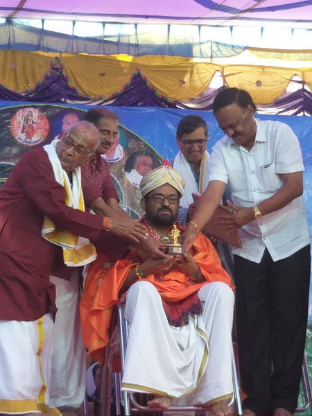 Dr. Nagendra Shastry receiving Purandara award from Reknowned Mridanga Vidwan AV Anand