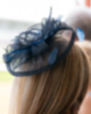 Lady in a black lace hat at a horse race