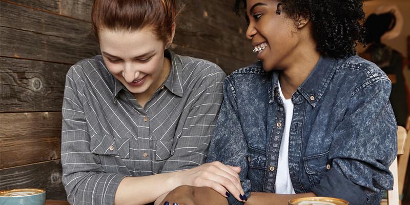 Foto ilustrativa mostra duas mulheres, sentadas, sorrindo e de braços dados uma a outra.