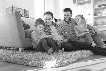Casal composto por dois homens, sentado no tapete da sala com um casal de filhos.