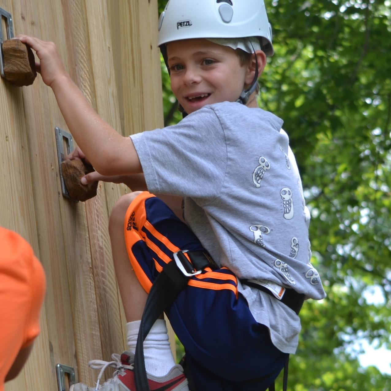 boy climbing wall gray shirt