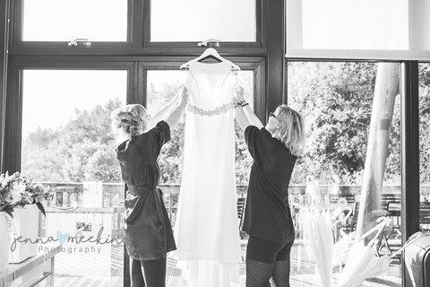 wedding dress being hung up at the window