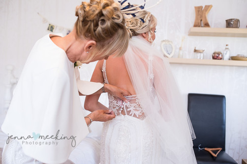 mother helping bride get ready at bridal preparations