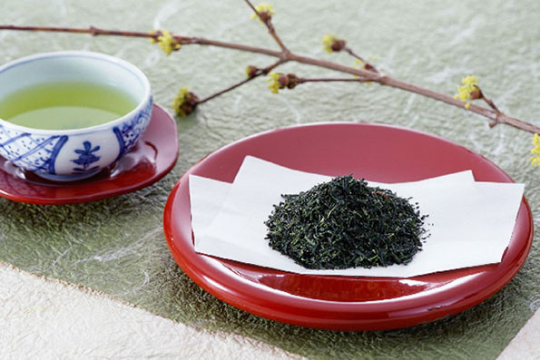 Whole leaf loose green Japanese tea in a plate and tea brewed in a teacup known as yunomi