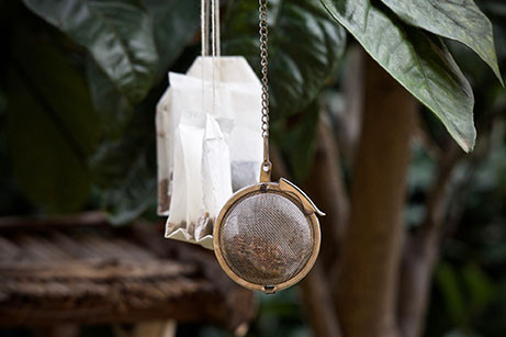 Hanging paper teabags and metallic rounded infuser