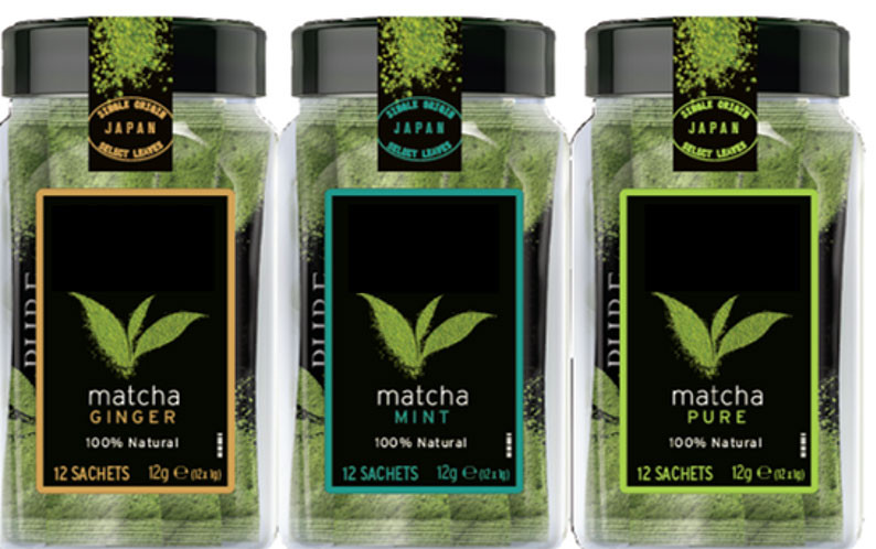 three glass jars containing artificially flavoured matcha powders