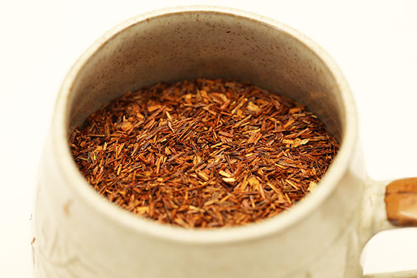 A cup containing dry rooibos leaves.