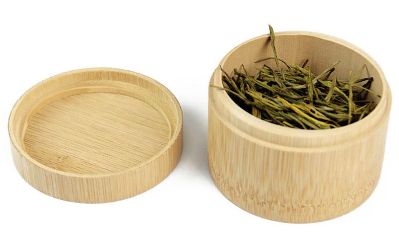 a bamboo tea caddy filled in with tea