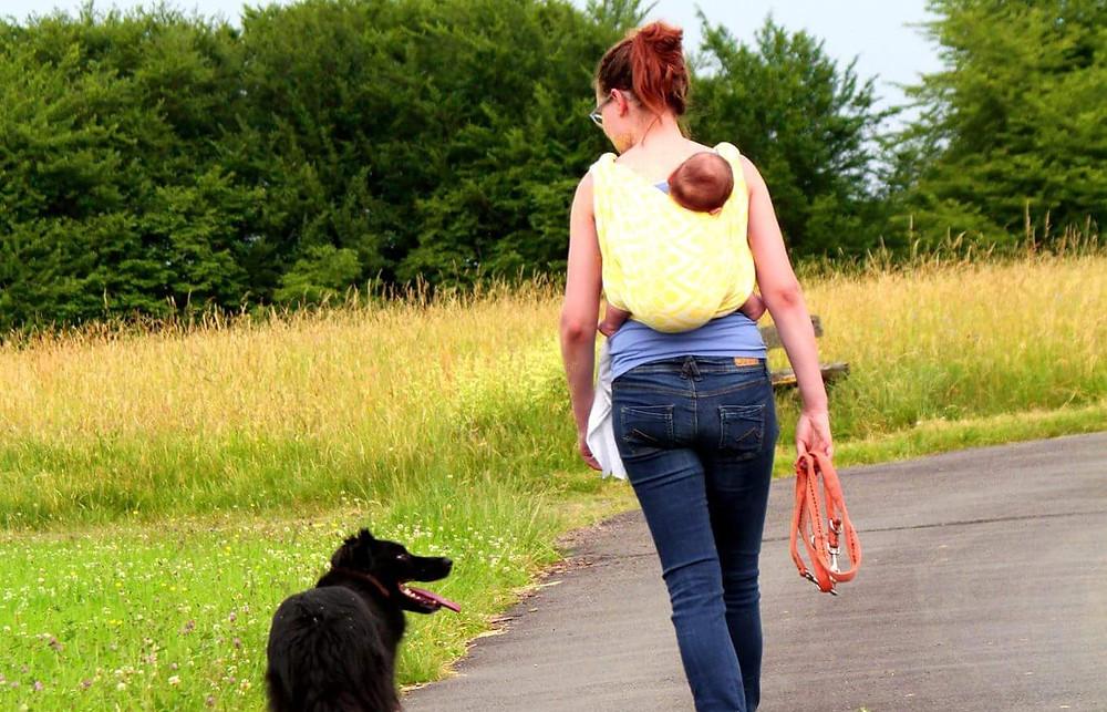 Esther von hinten, läuft mit Hund, trägt Baby im Wickeltuch